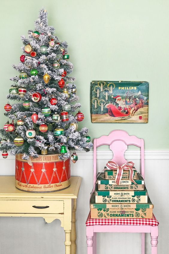 a flocked Christmas tree with colorful retro toys and lights and a stack of gift boxes for a vintage feel in the space