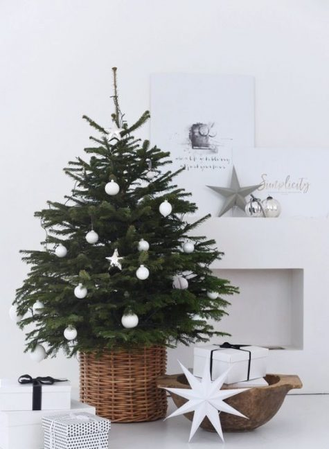 a minimalist Christmas tree in a basket with white ornaments is a stylish and cool idea with a rustic feel