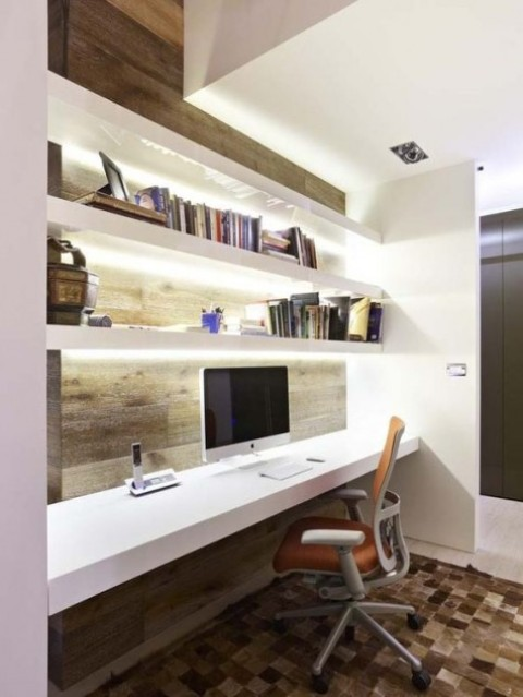 a minimalist workspace with a wood clad wall, white floating shelves with built-in lights and a matching desk plus a comfy chair