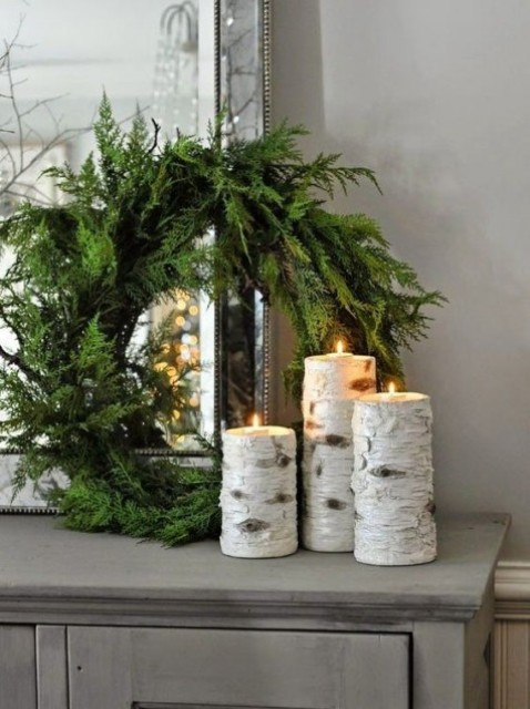 an evergreen wreath with birch candle holders for natural decor with a strong modern feel