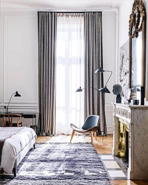 a chic Parisian sleeping space with grey textiles, a leather chair, a small desk in the corner, a non working fireplace and a comfy bed
