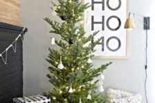 04 a minimalist Christmas tree with black and white ornaments and lights, monochromatic gift boxes and candle lanterns