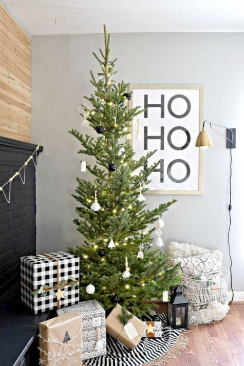 a minimalist Christmas tree with black and white ornaments and lights, monochromatic gift boxes and candle lanterns