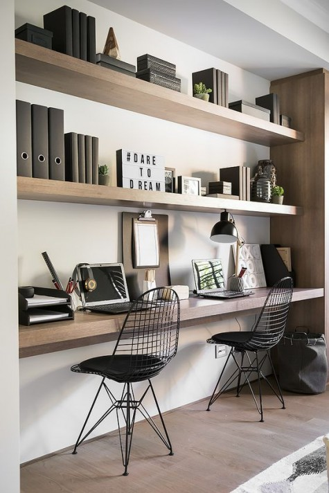 a minimalist home office space done with thick sleek shelves and a matching floating desk under them plus catchy black chairs