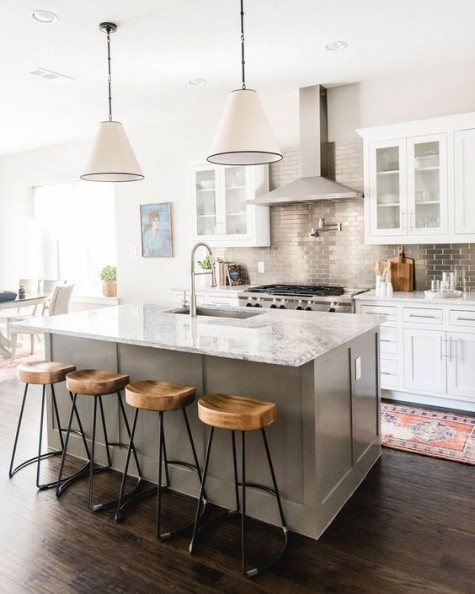a white kitchen with a grey kitchen island, a stone countertop and a metallic tile backsplash