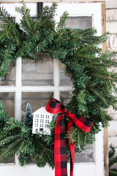 an evergreen wreath with a plaid ribbon and a small house is a cool Christmas decoration for a modern look with a rustic touch