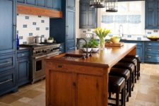 05 a bold blue kitchen and a warm-colored wood kitchen island and a matching hood to make the space cohesive