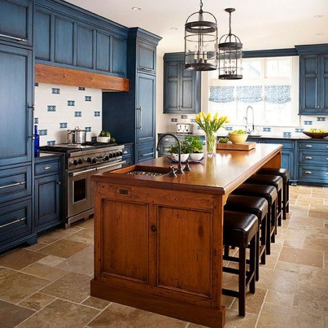 a bold blue kitchen and a warm-colored wood kitchen island and a matching hood to make the space cohesive