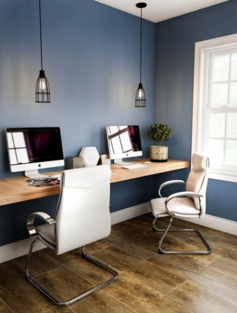 a contemporary home office nook with a floating desk, leather chairs and cage pendant lamps