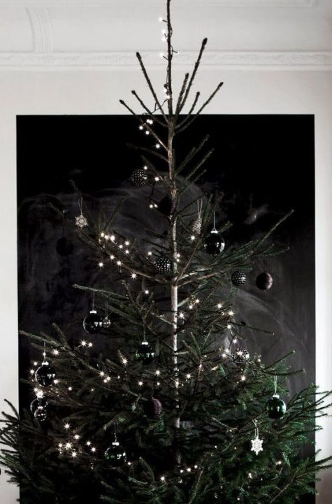 a minimalist and moody Christmas tree with lights, black ornaments and stars is a super edgy idea with two trends in one