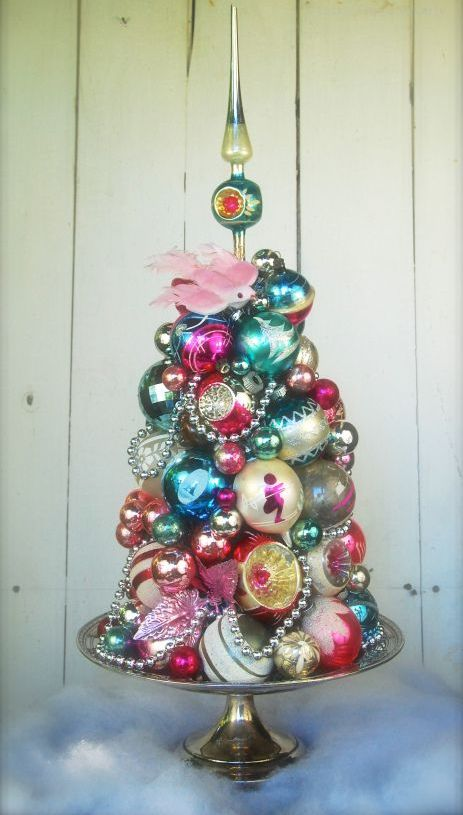 a vintage Christmas ornament tree on a dish with beads is a stylish and creative idea