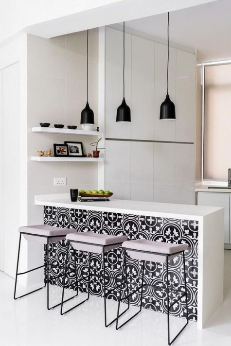 an all-white minimalist kitchen enlivened with bright black and white printed tiles on the kitchen island