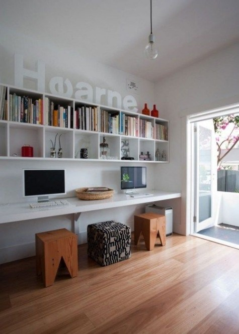 a contemporary home office with a large wall-mounted shelving unit, a floating desk and stools with much natural light