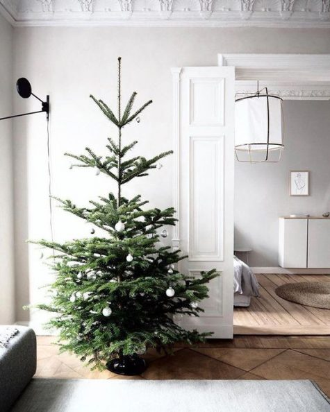 a minimalist Christmas tree with black and white ornaments is simple and stylish and will fit any minimalist space