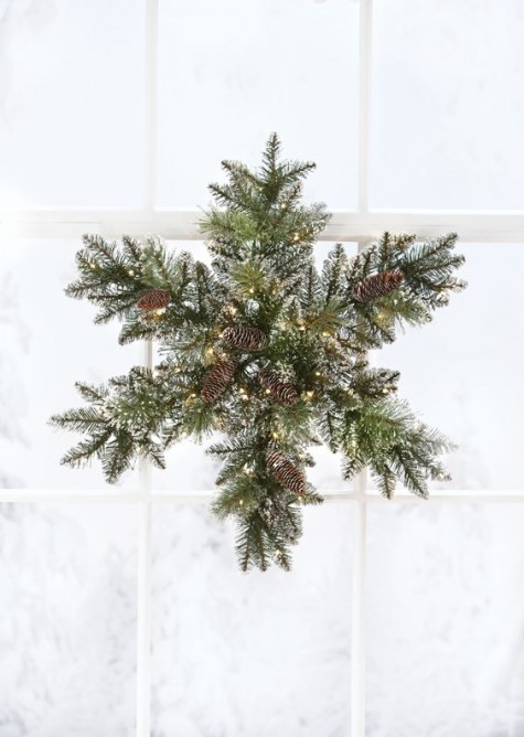 a snowy evergreen Christmas wreath with pinecones and lights shaped as a snowflake is an original and cool idea