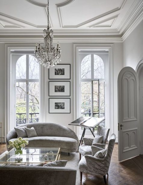 a white Parisian living room with molding, a crystal chandelier, marleized furniture and much natural light
