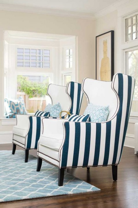 bold nautical wingback chairs with creamy fronts and striped backs plus decorative nail trim for a coastal interior