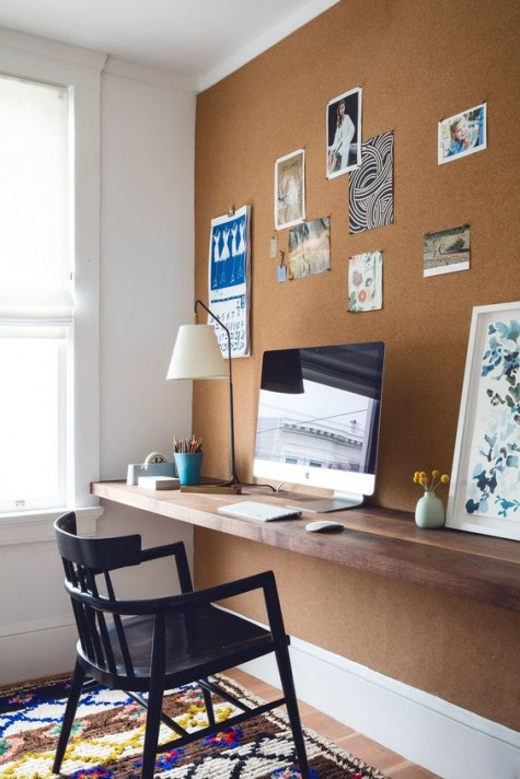 a cork wall for notes and a floating desk of reclaimed wood make up a comfy working nook with a modern feel