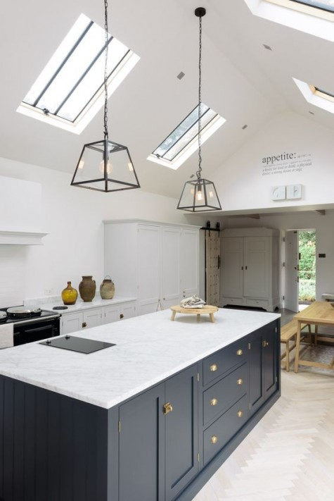 a pure white space and a navy kitchen island, white stone countertops everywhere for a cohesive space