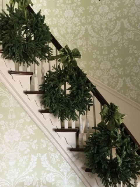 a trio of evergreen wreaths with green ribbons to decorate the stairs and give a slight vintage feel to the space