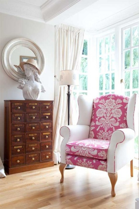 a vintage chair is made more modern with a pink printed seat and back and white armrests with a pink edge looks very soft and girlish