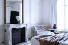 07 a white Parisian bedroom with a statement mirror over the fireplace, an upholstered bed, a chic tufted sofa and much natural light