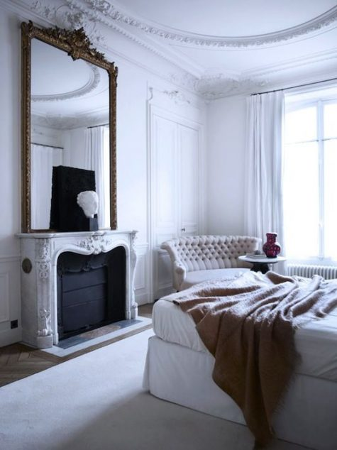 a white Parisian bedroom with a statement mirror over the fireplace, an upholstered bed, a chic tufted sofa and much natural light