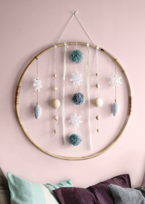 an IKEA LATTJO hoola hoop turned into a creative holiday wreath with wooden ornaments and pompoms