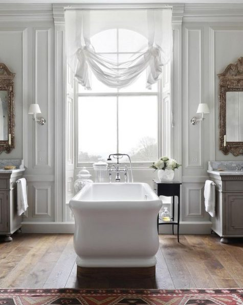 a beautiful vintage inspired bathroom with a white tub, curtain, mirrors and chic vanities plus a rug