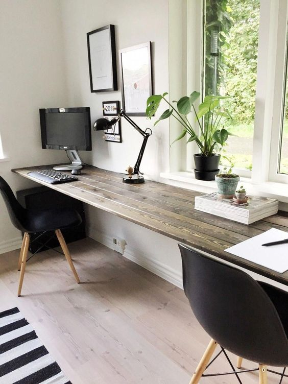 a dark stained windowsill floating desk, black chairs and a gallery wall make up a cozy working space that is enough for two