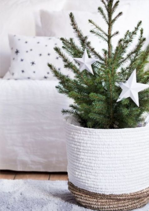 a minimalist Christmas tree with white ornaments in a woven basket is a cool idea for small spaces that can't accomodate a larger tree