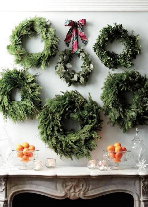 an arrangement of evergreen wreaths over the fireplace made if various types of greenery and evergreens is super chic