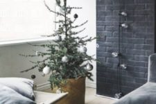 09 a minimalist Christmas tree with white, black and metallic ornaments and bulbs is a stylish and simpel idea for a minimalist space