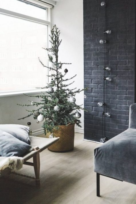 a minimalist Christmas tree with white, black and metallic ornaments and bulbs is a stylish and simpel idea for a minimalist space