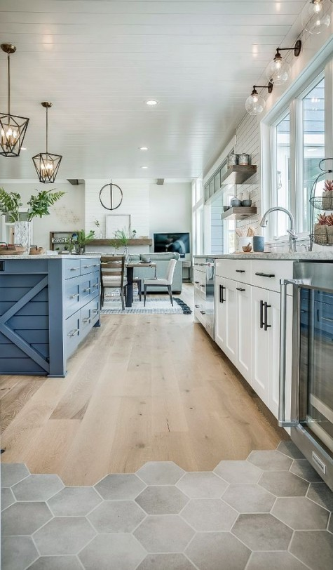 a modern farmhouse white kitchen and a bright blue kitchen island with matching grey stone countertops