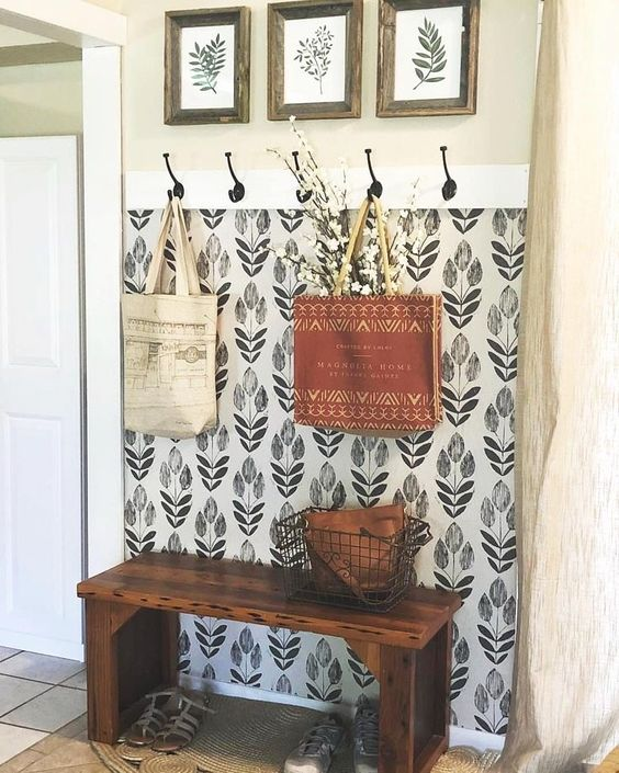 a small entryway spruced up with a ouch of botanical print monochromatic wallpaper and a matching gallery wall