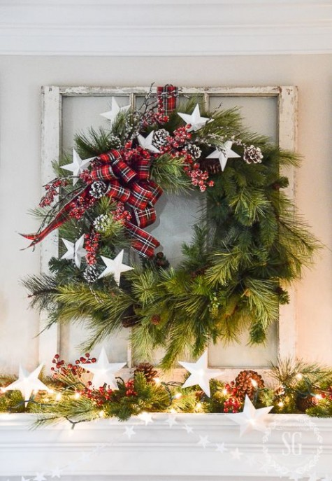 a whimsy evergreen wreath with plaid ribbons, stars and snowy pinecones plus a matching garland on the mantel for holidays