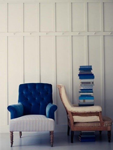 a bold chair in blue velvet and a striped seat plus vintage carved wooden legs is a bold statement for an eclectic space