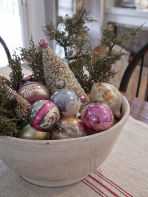 a bowl with vintage glass ornaments plus evergreens is a charming vintage centerpiece or just a decoration