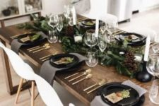 10 a chic modern Christmas table with an evergreen runner and pinecones, black plates, white candles and gold cutlery