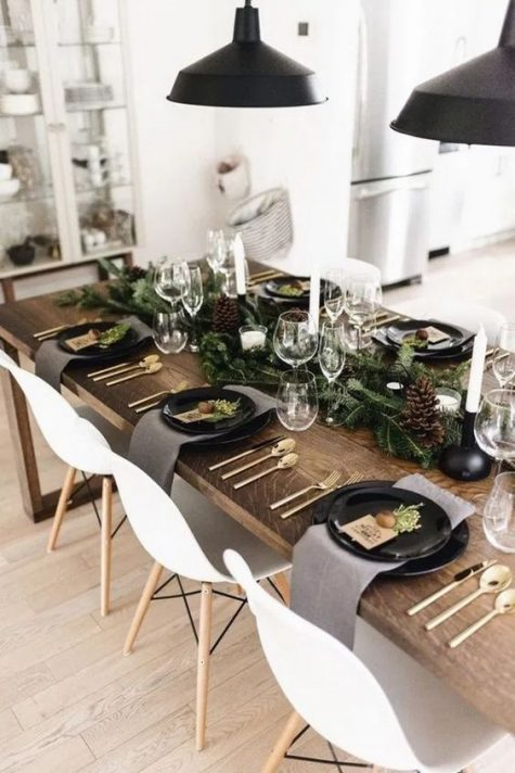 a chic modern Christmas table with an evergreen runner and pinecones, black plates, white candles and gold cutlery