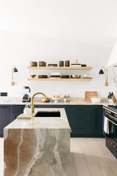 a large stone kitchen island is connected to the cabinets with the countertops of the same stone and shade