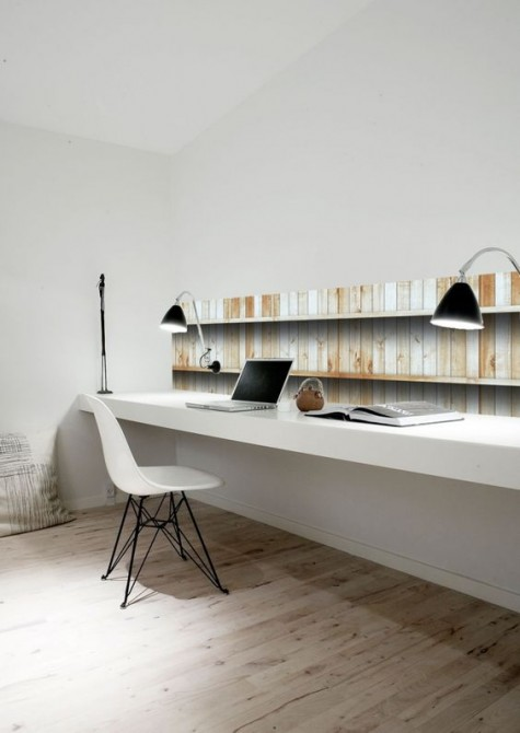 a minimalist home office nook with a touch of faux reclaimed wood on the wall, a floating desk, a couple of wall-mounted lamps and a white chair