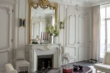 10 a refined neutral Parisian living room with a non-working fireplace that is accented with a refined mantel and a gorgeous mirror in gold