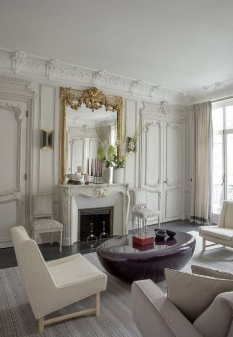 a refined neutral Parisian living room with a non-working fireplace that is accented with a refined mantel and a gorgeous mirror in gold