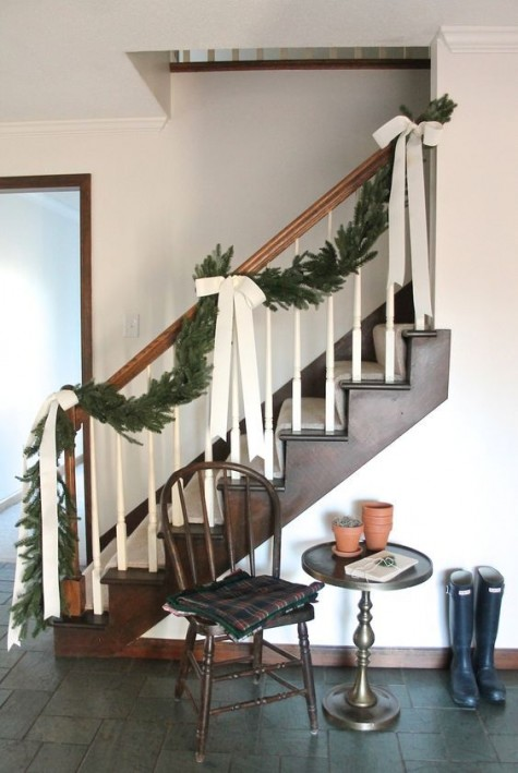 a chic evergreen garland with creamy ribbon bows is a nice idea for a farmhouse Christmas, it looks bold and chic