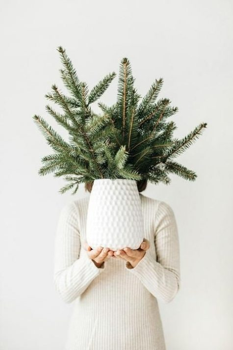 a minimalist Christmas centerpiece of a white vase and evergreens is easy to compose yourself