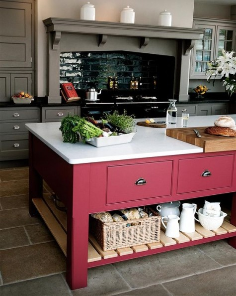 a vintage rustic kitchen in grey and an oversized bright pink kitchen island with plenty of closed and open storage
