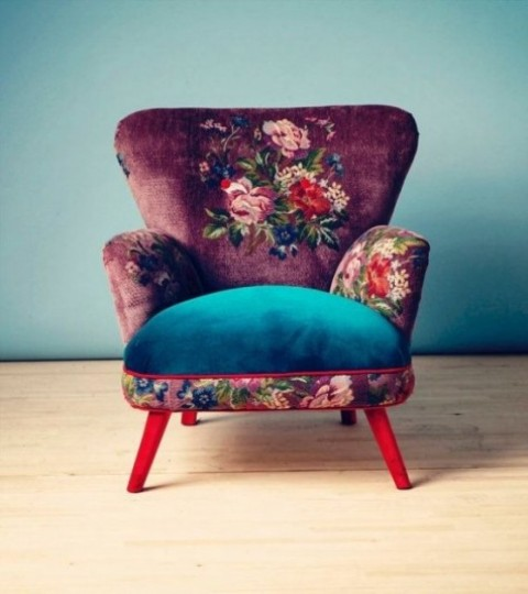 a bright chair with a burgundy floral back and armrests, a bold blue seat and hot red legs brings texture, color and prints in