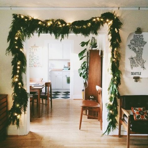 a lit up evergreen garland over the entry is a stylish idea that is always actual and works for any style and any space